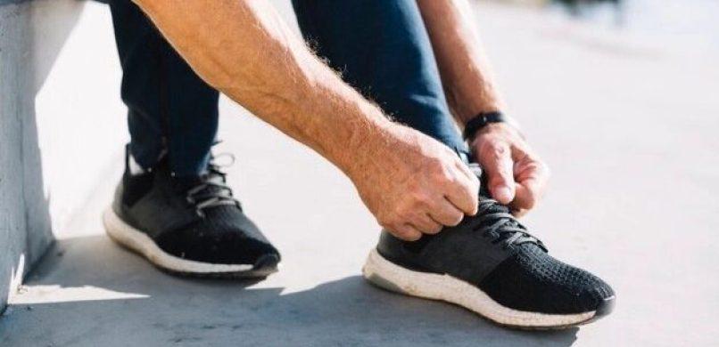 homme qui fais se lacets pour chosir ses chaussures de sport