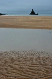 Stackpole fotografiado desde la playa Broad Haven South. Se puede ver una persona con su perro cerca de la playa.