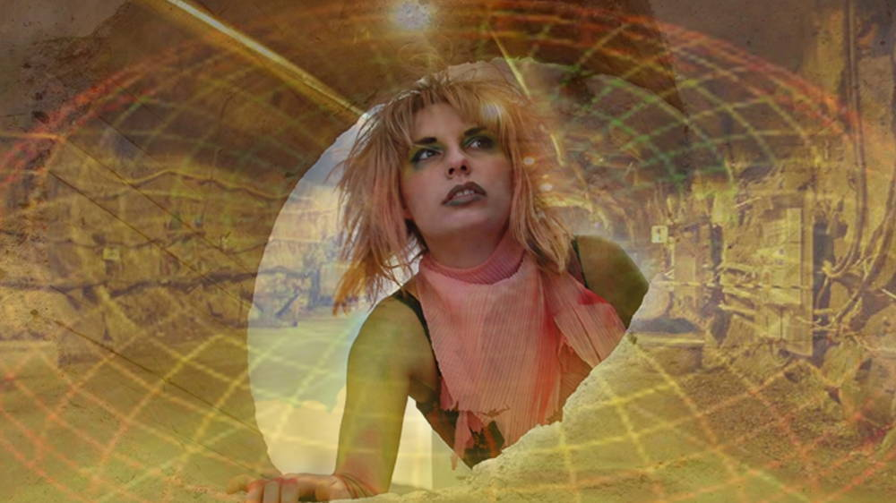 Eve Laramee, ReptileWoman from Slouching Towards Yucca Mountain, 2015, still from video. This reptile woman, a time traveller from a distant future, witnesses our legacy through desolate post-atomic landscapes. Click to enlarge.