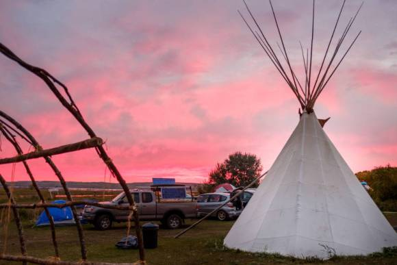 Dawn at the Sacred Stone camp. On the left is a longhouse frame. An Ojibwe supporter from Minnesota donated materials and his labor in order to construct several longhouses. This combination of teepees, nylon tents, tarps, and the longhouse is an example of the culturally and technologically eclectic nature of the camps. Image by author, September 2016.
