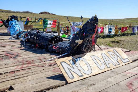 """Activists at the Red Warrior Camp produced this sculpture, titled """"Black Snake Killa,"""" which evokes a Lakota story of an apocalyptic black snake. The snake has been placed here, at one of the active construction sites, along with banners and signs declaring solidarity from tribes, communities, and social movements from around the world. Image by author, September 2016."""