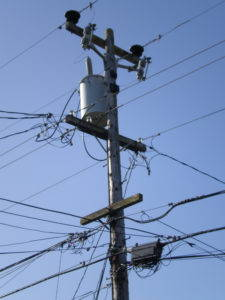 """Colloquially referred to as """"telephone poles,"""" the typical utility pole supports electric distribution lines, """"pole pig"""" transformers, street lighting, traffic signals, and even the occasional fire alarm, all in addition to raising telephone cables out of pedestrian reach. Source: Wikimedia Commons."""