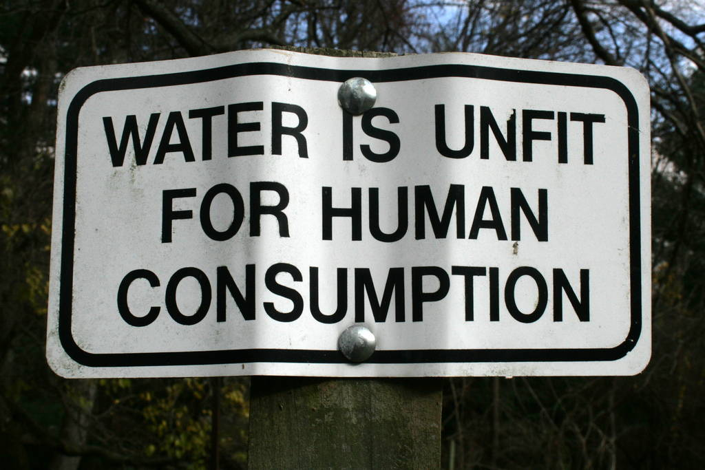 """Crumpled sign that reads """"Water is Unfit for Human Consumption"""""""