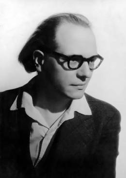 A black and white portraite of the composer Olivier Messiaen, wearing dark-rimmed glasses and an oped-collar shirt with a dark sport coat, looking down to the right.