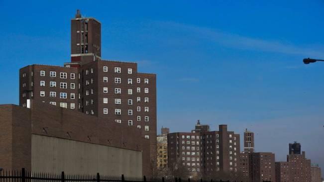 Three brick public housing towers against a blue sky.