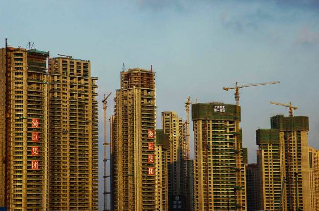 Four high-rise buildings against a skyline with cranes and Chinese characters.
