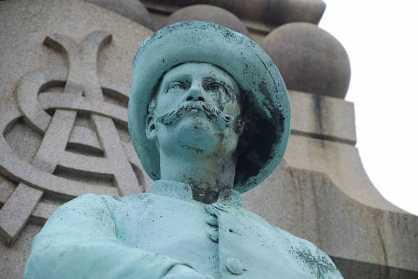 A bronze statue of a Confederate solider stands in front of a granite monument.