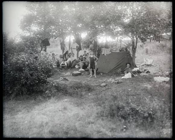 Black and white photograph of twenty people posing beside a tent beneath oak trees.