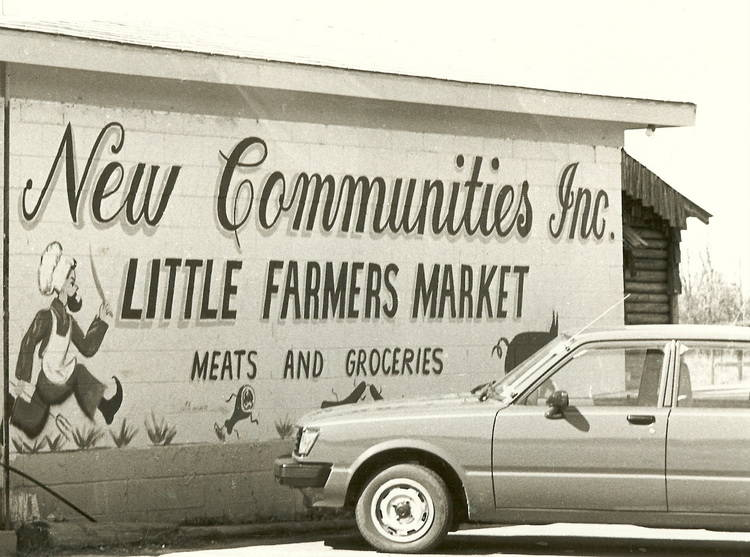 """Black and white photo of the side of a cinder-block building painted to read """"New Communities Inc. / Little Farmers Market / Meat and Groceries"""" with a cartoon of a butcher wielding a knife chasing after a pig. A sedan is parked in the foreground."""