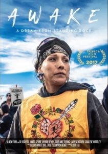 """The movie poster from """"Awake: A Dream from Standing Rock"""" depicting a Native woman in a sweatshirt and with ski goggles on her head, looking off to the right with protesters and a bright blue sky in the background."""