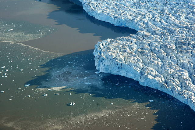 An ariel photo of the Polar Ice Rim. A glacier sweeps the right side of the image. The water surrounding the glacier is speckled by icebergs.