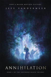 A book cover for Annihilation. Actress Natalie Portman leads a team of explorers wielding weapons through the forest.