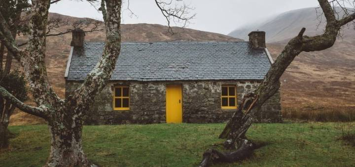 A stone hut with a yellow door is framed by two trees.