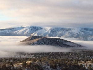 Fog fills a mountain valley while peaks rise in the background.