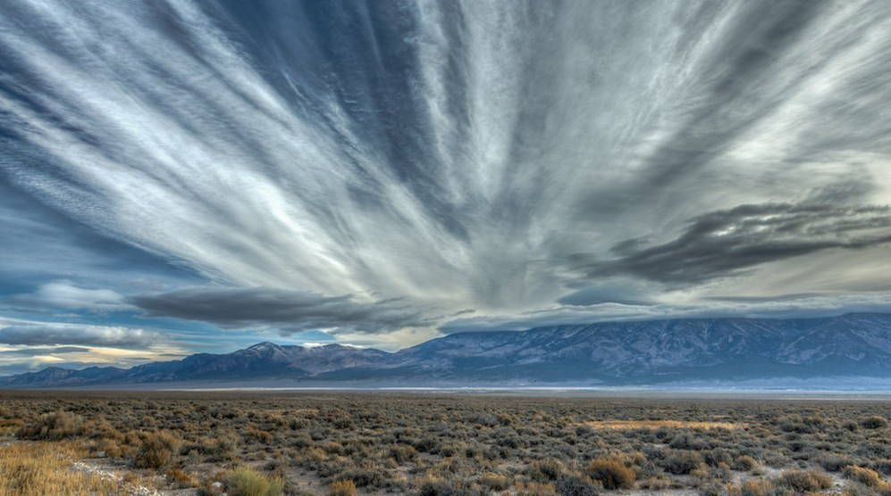 Cirrus clouds streak across the sky above a sage steppe landscape.