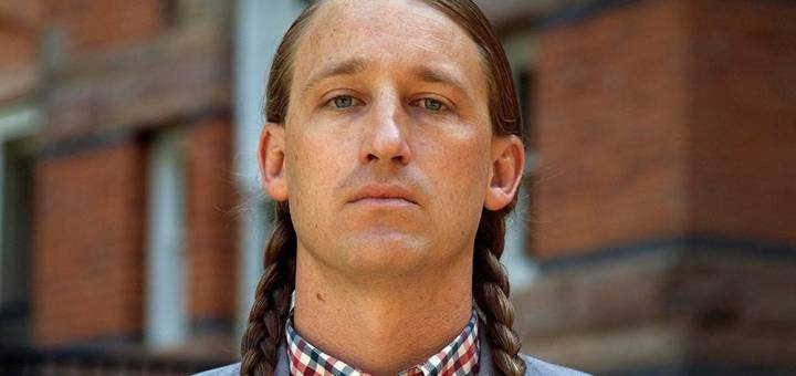 A photo portrait of Dylan Miner, looking at the camera wearing a plaid shirt and blue sportcoat with long braids on both sides of his head.