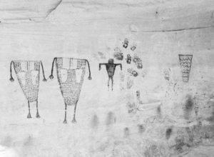 A black and white photograph of drawings of human figures and handprints on a cave wall.