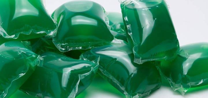 A pile of eight emerald green laundry detergent Tide Pods against a white background.
