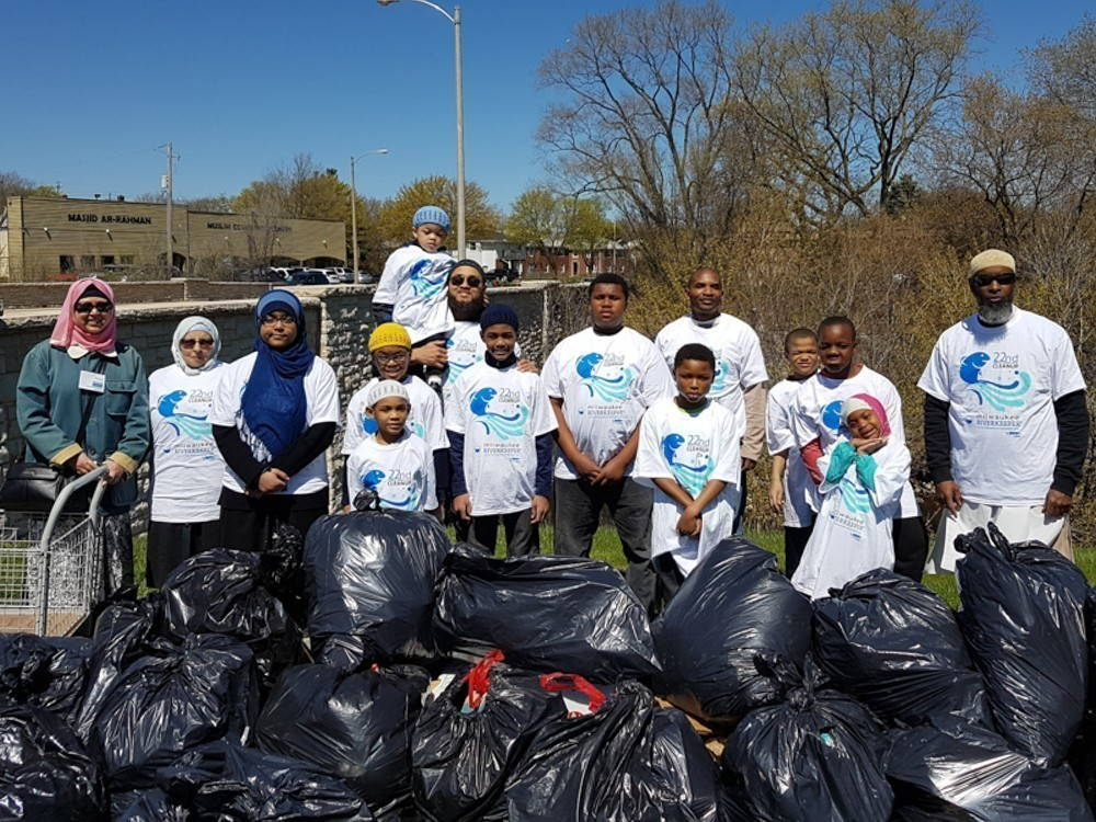 Huda Alkaff poses with five adults and nine children in front of a wide pile of black bags of garbage in front of a short stone bridge spanning a river.