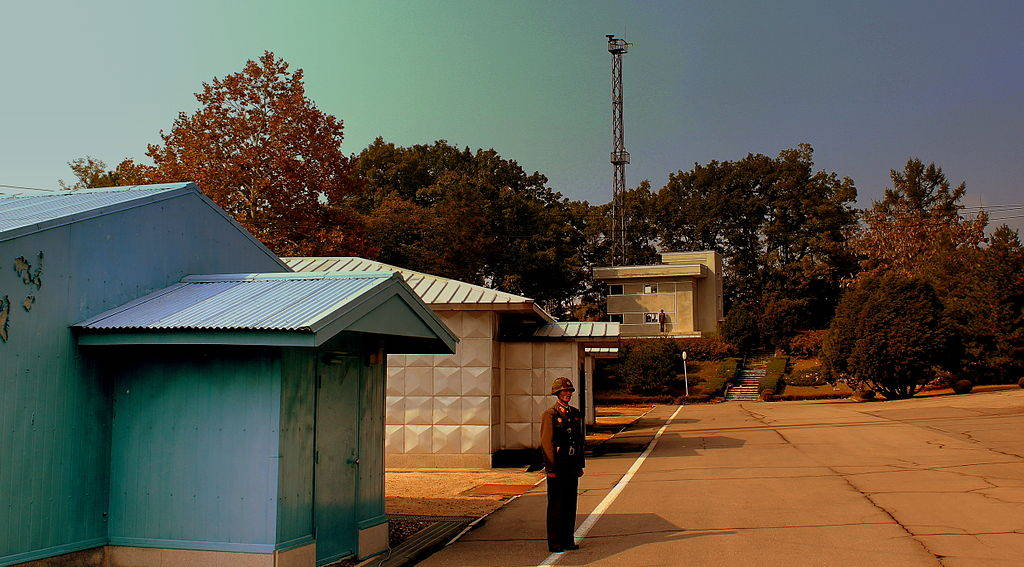 A uniformed North Korean soldier stands before the crossing point at the DMZ, a site marked by a white line and low one story buildings