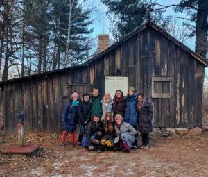 A group of students poses for a photograph in front of Leopold's shack, a simple wooden structure.