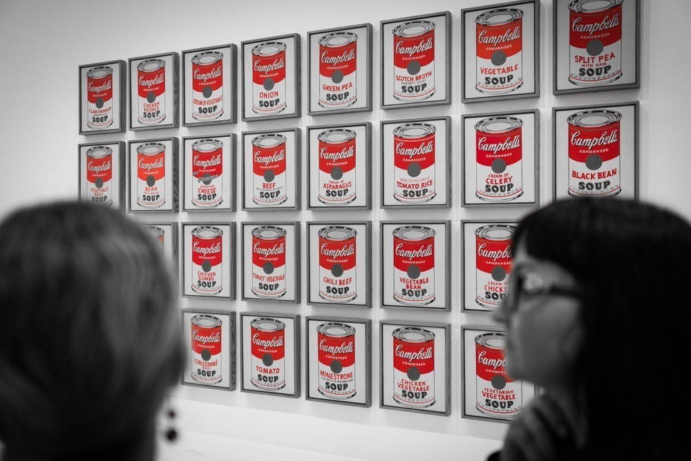 """Two visitors to the Museum of Modern Art (MoMA) in front of Andy Warhol's """"Campbell Soup Cans"""" (1962)"""