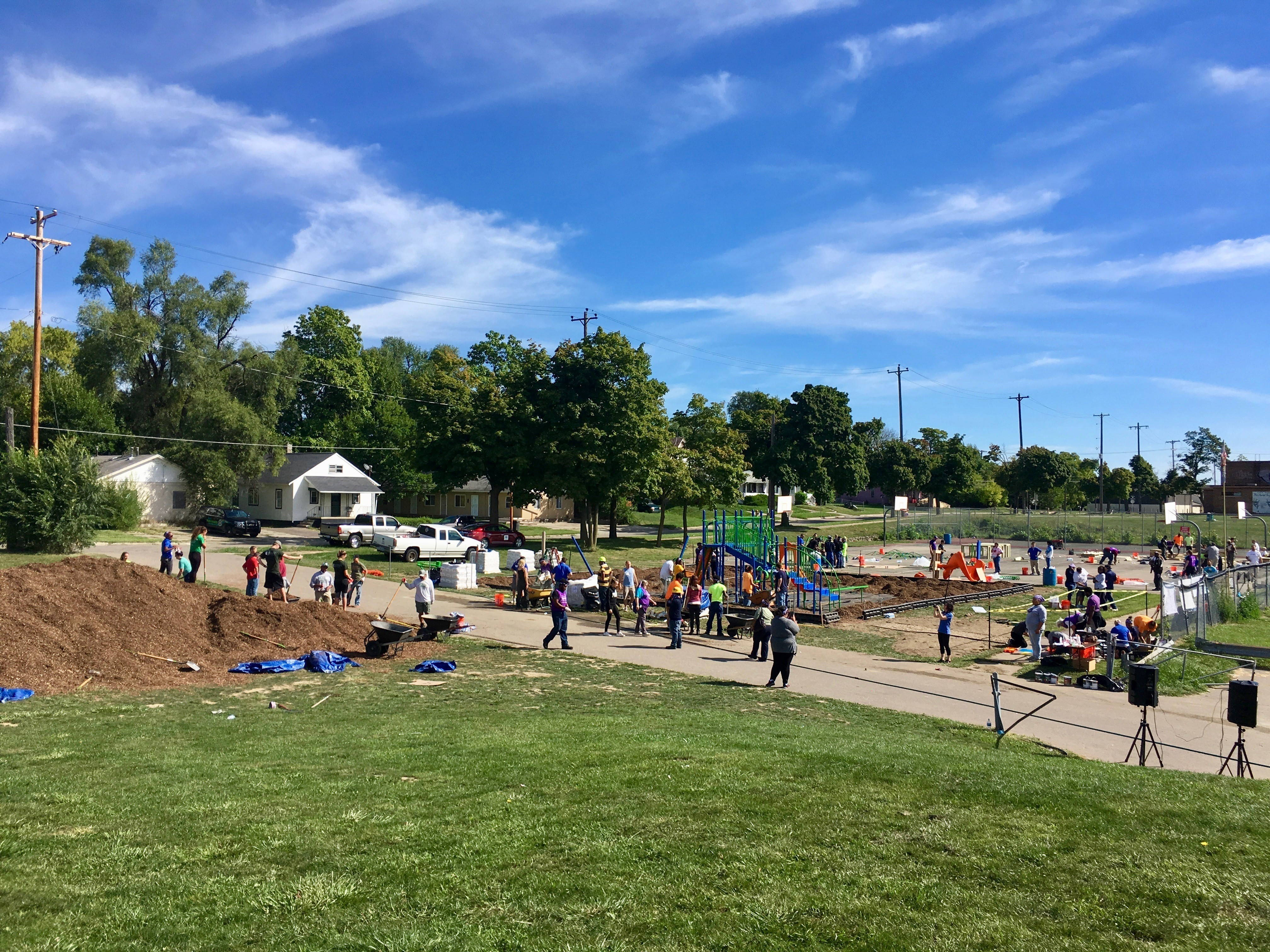 A group of people in the background work together to shovel dirt and put together a playground structure.