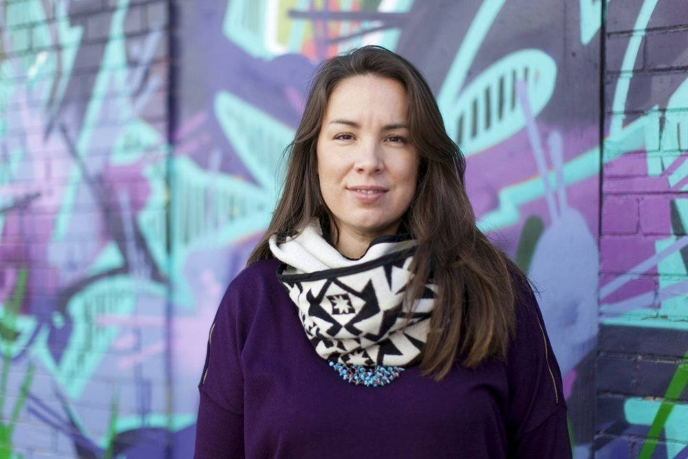 A brunette woman with a purple sweater and a white and black scarf smiles slightly at the camera. She stands in front of a colorfully spray painted wall.