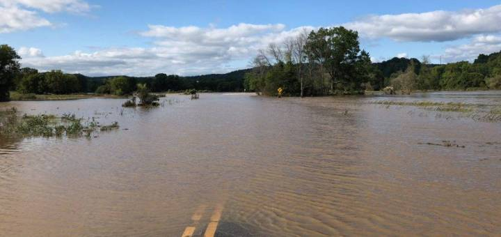 Kickapoo River covers a roadway in muddy water.