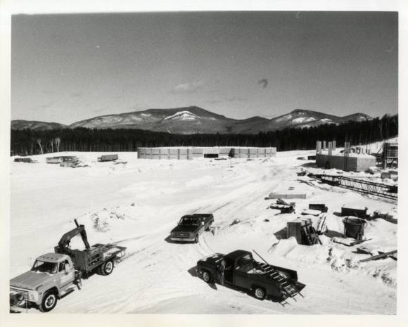 Black and white photo of pick up trucks on a snowy field with mountains in the background.