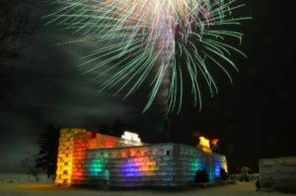 A translucent fortress with a turret glows from the inside in several colors with a white firework exploding against the black sky overhead.