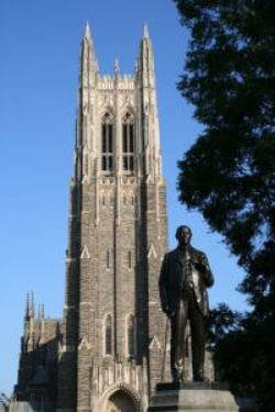 A dark statue of a man standing and holding his lapel with his left hand in front of a gothic stone tower bathed in sunlight.
