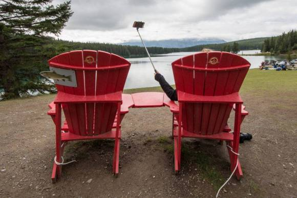 A person sitting in a red lounge chair takes a selfie. In the background is a lake and mountains.