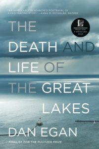 The cover of The Death and Life of the Great Lakes by Dan Egan, a blue and grey photograph of a lake (presumably a great one) shot from a vantage point of above the water and below the clouds, looking towards the horizon, with a small boat and dock visible in the foreground