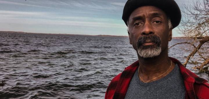 Portrait of a Eddy Harris in a black beret and a red and black flannel shirt open over a grey t-shirt looking at the camera without smiling with a big lake in the background under a grey sky.
