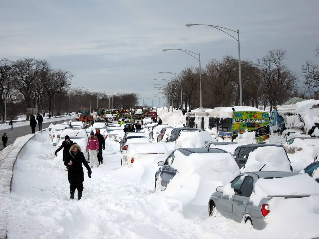 People walk along rows of cars stuck in many feet of snow.