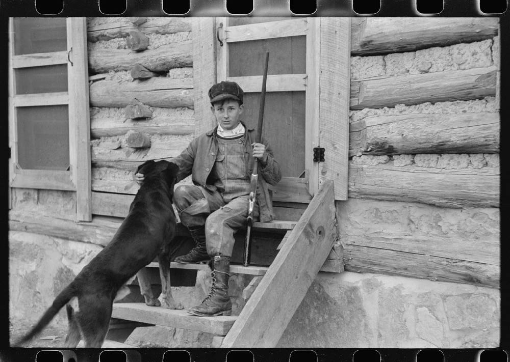 A black-and-white photograph of a young boy sitting on steps while holding a long gun with a dog