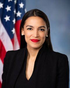 The official portrait of Alexandria Ocasio-Cortez, in a black blazer with an American flag in the background