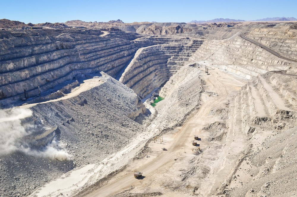 A gigantic uranium mine reaches far into the earth with terraced levels, mounds of gray earth, and a small green pool at the bottom.