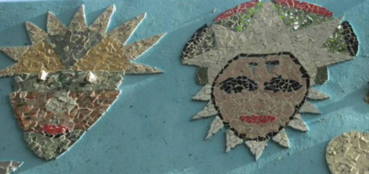 Ceramic and glass mosaics of two faces on a blue concrete wall