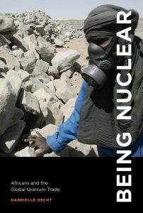 The title of the book is in bold white font and alligned vertically on the right side of the cover. Behind the title a man wearing a mask stands beside a large wall of rocks.