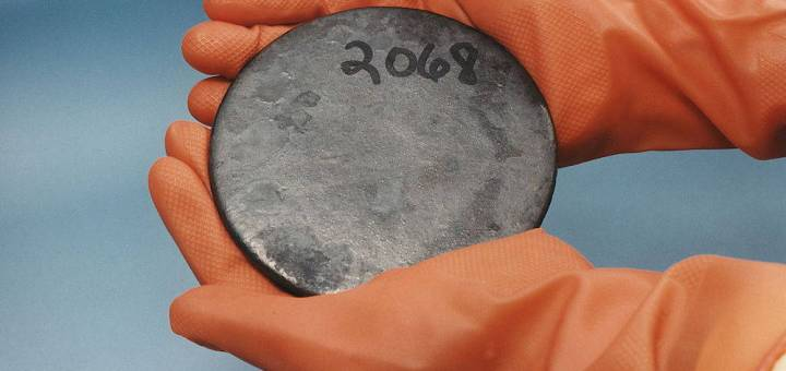 Two orange gloved hands hold a round disc of uranium with the number 2068 written on it.