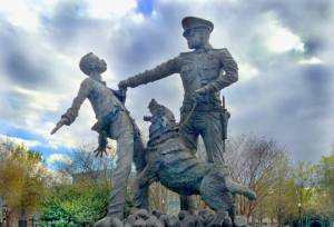 A sculpture depicting a police officer with a dog on a leash, as the dog attacks a man who is falling backwards