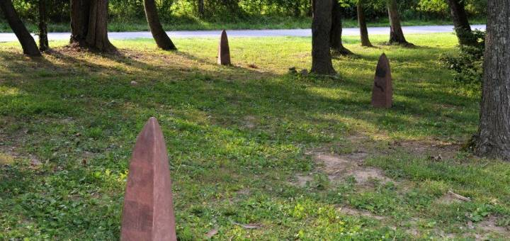 Small conical red clay sculptures in a wooded lot.