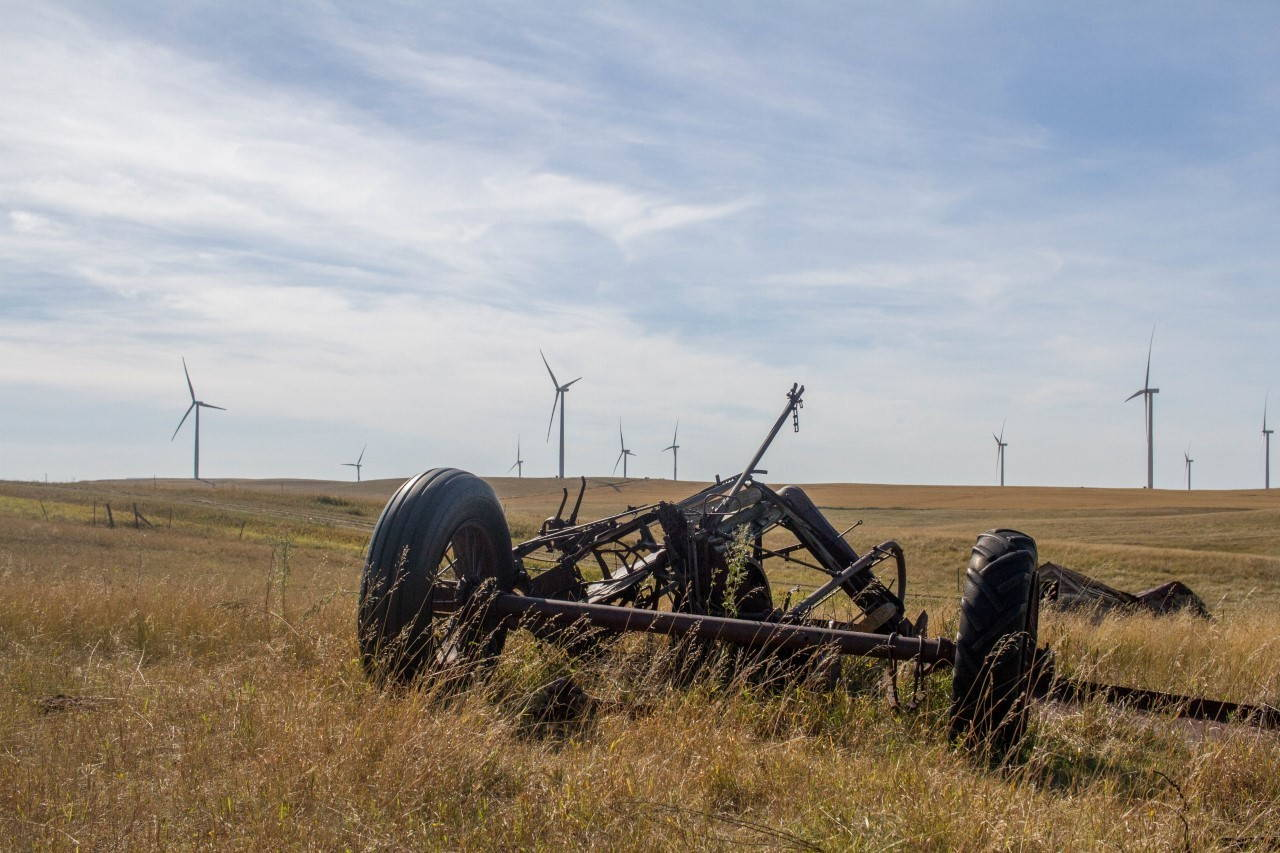 An rust, abandoned plow sits in the foreground with a hayfield full of wind turbines against a bright sky.