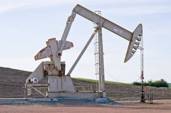 A large white steel pumping rig sits in the foreground with a furrowed field behind it.