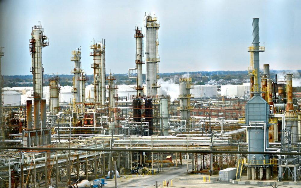 Smokestacks and pipe networks of an oil refinery. City skyline in background.