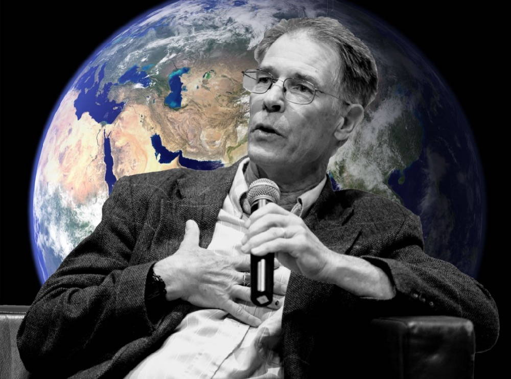 Kim Stanley Robinson holds a microphone and in the background a satellite image of the earth is visible