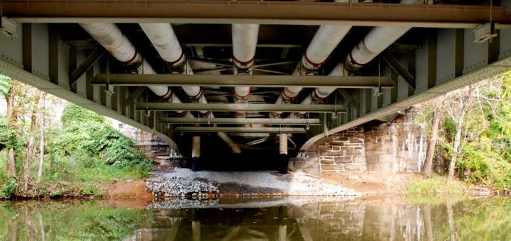 Several pipes run underneath a bridge and over a river in the Washington, DC, area.