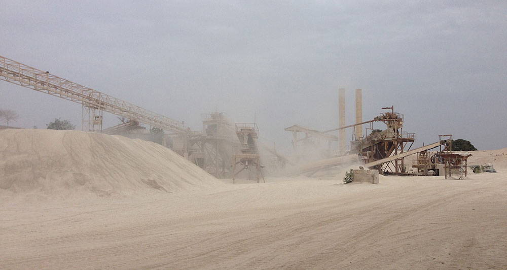 Hills of sand are surrounded by dust and large mining machinery.